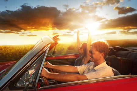 hombre manejando: Pares que conducen un coche convertible disfrutando de un d�a de verano al atardecer Foto de archivo