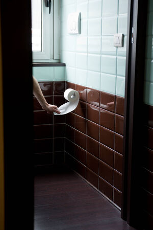 pooping: Hidden man using toilet paper in the restroom for cleansing.