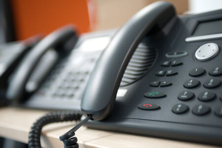 Set of black telephones on a desk, receiver close-up.