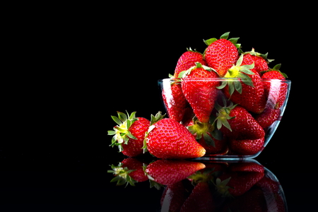 Delicious strawberries in a glass bowl on black background. photo