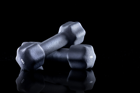kilogram: One kilogram dumbbells for weight training on black background. Stock Photo