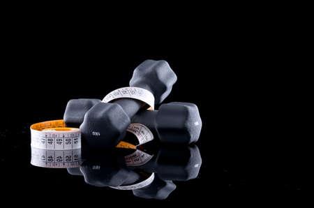 kilogram: One kilogram dumbbells and tape measure on black background. Stock Photo
