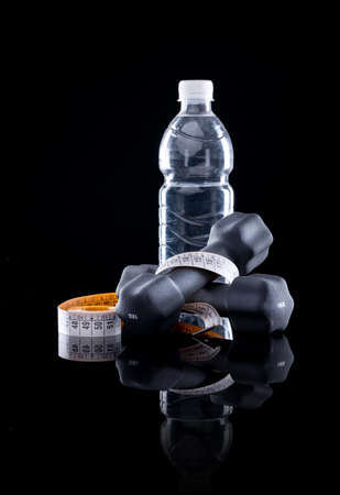 water power: Water bottle, measure tape and dumbbells on black background. Stock Photo