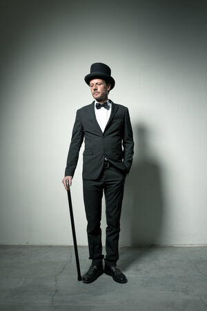 Classy gentleman with bowler hat and cane looking down photo
