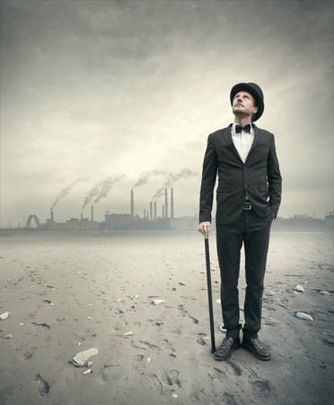 Vintage businessman looking away with polluting factory and post atomic landscape on background. photo