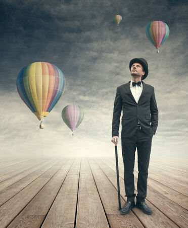 Attractive elegant businessman looking up at hot air balloons in the sky. photo