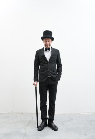 Classy smiling gentleman standing on white background and concrete floor in elegant suit with cane and bowler hat. photo