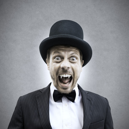 Scary vampire businessman screaming and showing fangs in vintage elegant outfit. photo