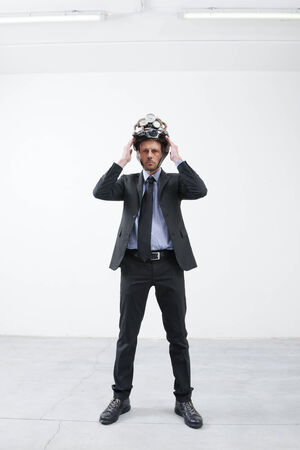 overburdened: Tired pensive businessman touching his forehead weaaring futuristic helmet with gauges. Stock Photo