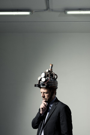 Confident businessman thinking with hand on chin wearing steampunk helmet photo
