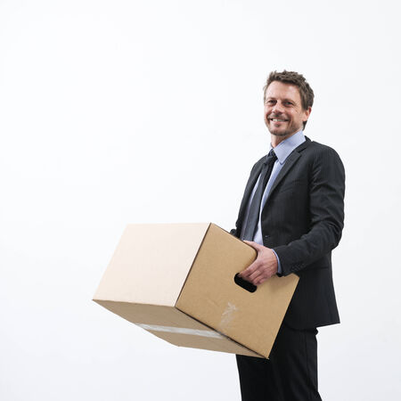 relocate: Smiling businessman holding a cardboard box and standing into an empty new office. Stock Photo