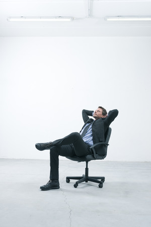 idea comfortable: Thinkful businessman sitting on office chair with hands behind head in his new empty office.