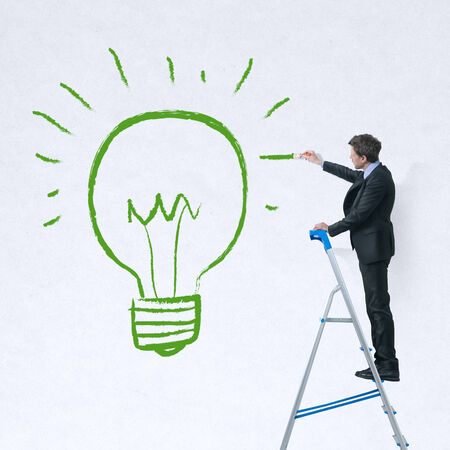 Businessman on a ladder painting a green lit bulb on a white wall. photo