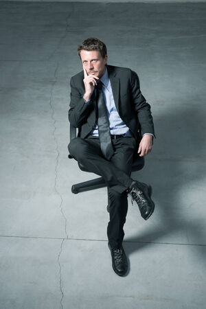 executive chair: Businessman sitting on an office chair against concrete floor background. Stock Photo