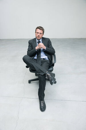 man in chair: Businessman sitting on an office chair against concrete floor background. Stock Photo