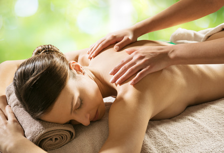 Beautiful woman receiving a relaxing back massage at spa. photo