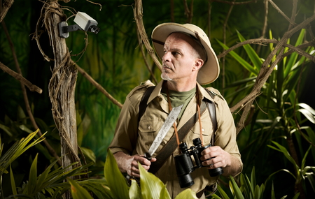 Explorer walking in jungle being watched by a security camera. photo