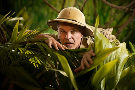 jungle: Adventurer hiding and peeking through plants in the rainforest jungle with exploration equipment.