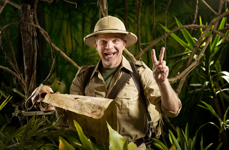 Successful pioneer in the jungle finding right direction on map. photo