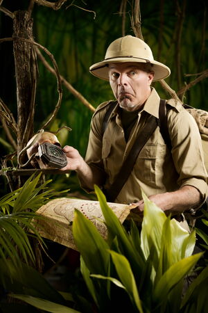 Lost adventurer holding an old map and a compass in the jungle. photo