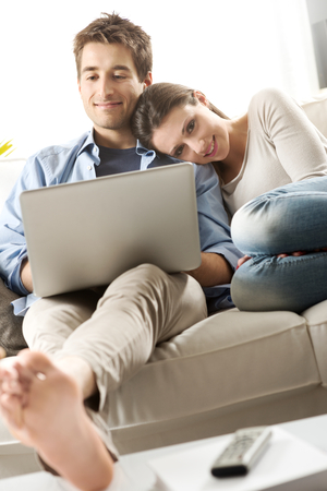 barefoot man: Young couple relaxing on sofa with laptop in the living room. Stock Photo