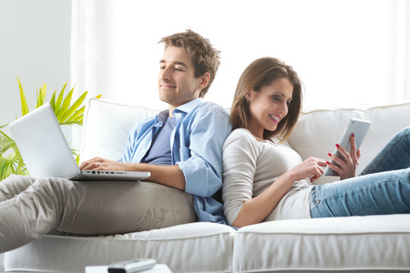 domestic room: Young couple relaxing on sofa with digital tablet and laptop.