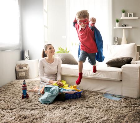 enfants qui jouent: Gar�on super-h�ros et sa m�re � faire la lessive ensemble dans la salle de s�jour. Banque d'images