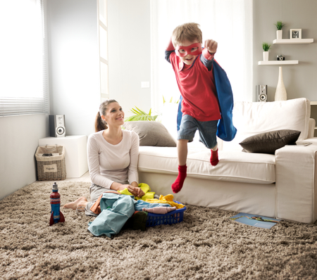 family indoors: Superhero boy and his mother doing laundry together in the living room.