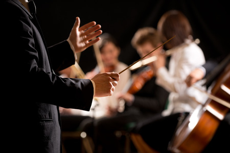 a symphony: Conductor directing symphony orchestra with performers on background, hands close-up.