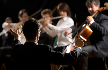 a symphony: Conductor directing symphony orchestra with performers on background. Stock Photo