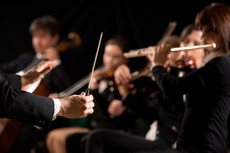 maestro: Conductor directing symphony orchestra with performers on background. Stock Photo