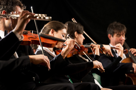 Symphony orchestra on stage, violins, cello and flute performing. photo