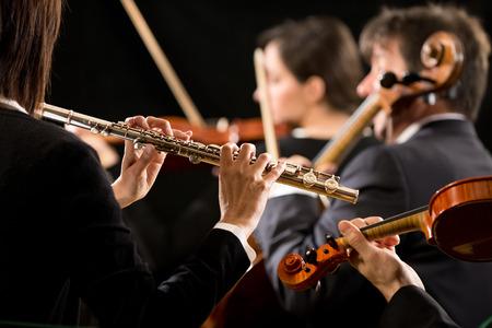 orquesta: Flautista profesional femenino en concierto con m�sicos de la orquesta sinf�nica en el fondo.