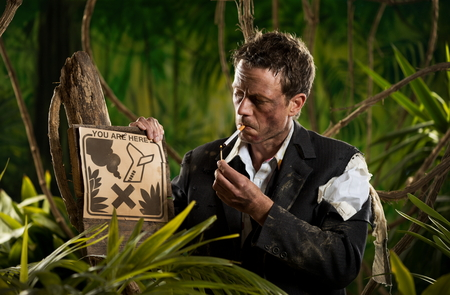 imperturbable: Businessman lost in jungle lighting a cigarette next to a no smoking sign. Stock Photo