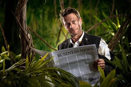 Smiling businessman reading a financial newspaper in the jungle with torn clothing. photo