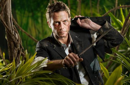 Confident strong businessman dealing with jungle dangers, holding a machete. photo
