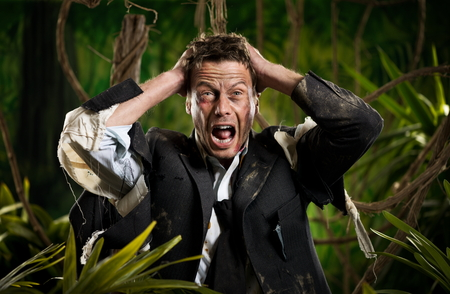 adventurer: Desperate businessman with head in hands and torn clothing lost in jungle. Stock Photo