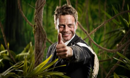 adventurer: Attractive confident businessman with torn clothing in the jungle smiling with thumbs up.