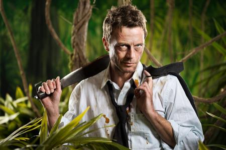 machete: Attractive confident businessman with machete walking in the jungle.