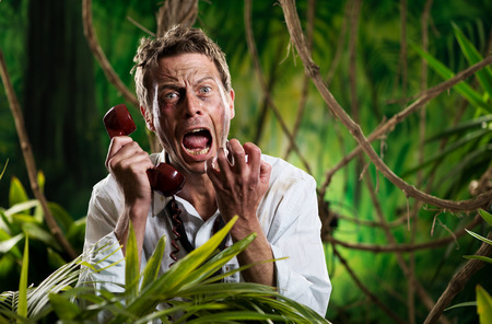 Angry businessman lost in jungle screaming at the phone. photo