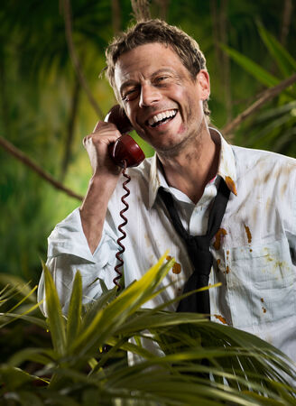 Attractive businessman talking on the phone in the jungle with torn clothing. photo