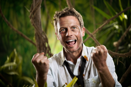 Successful winning businessman in torn clothing smiling with fists raised in the jungle. photo