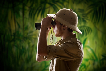 Young confident explorer in the rainforest jungle looking through binoculars. Stock Photo