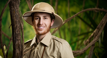 pith: Young confident explorer in the jungle with pith hat smiling at camera.