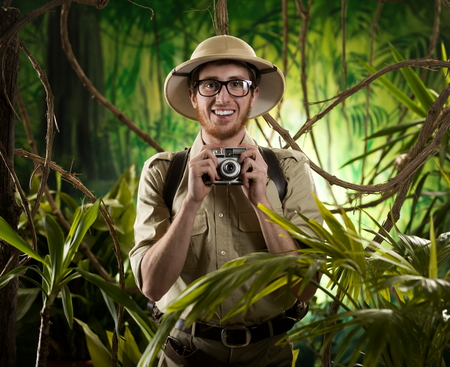 adventurer: Young explorer in the jungle taking pictures with vintage camera. Stock Photo