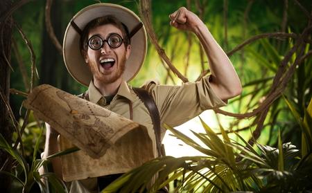 bonne aventure: Jeune explorateur de sourire dans la jungle avec des lunettes épaisses et le poing levé en détenant une carte. Banque d'images