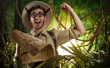 Young smiling explorer in the jungle with thick glasses and fist raised holding a map. photo