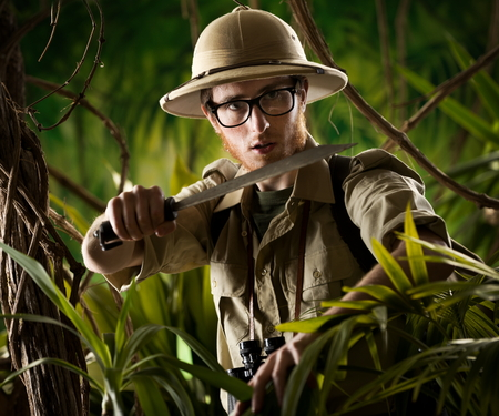 discovering: Watchful young adventurer holding a machete walking through the jungle.