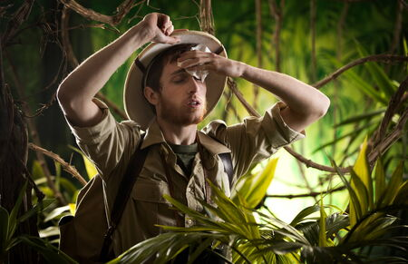 extreme heat: Tired young explorer in the jungle wiping sweat off his forehead.