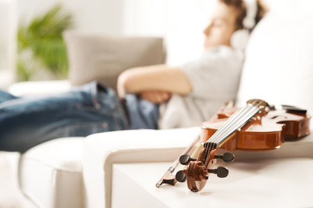 Violin close-up with man relaxing and listening to music on background. photo